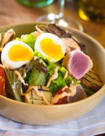 Mix de folhas, atum selado, batata bolinha grelhada, vagem holandesa, tomate assado, ovo mollet e molho tuna.
